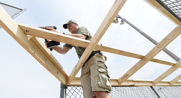 AT&T employee Andy Robeson helps build a new top for a dugout on Tuesday afternoon at the old Redden Field. The field is the last free-use ball field in Joplin and AT&T employees welcome members of the community to help restore the field on Saturday.<br /> Globe | Laurie Sisk