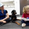 Seven-year-old Abbie Hicks reads to Kuma, a doberman pinscher as Kuma's owner, C.J. Irlam looks on during Dog Day Afternoon on Tuesday at the Joplin Public Library. The program allows young readers to read aloud in a comfortable, no-critical environment.<br /> Globe | Laurie Sisk
