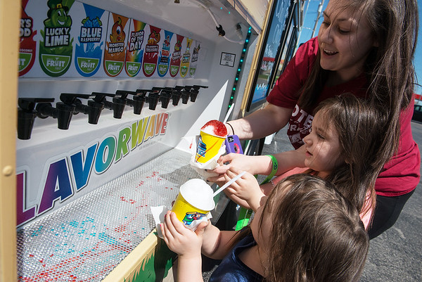 (from left) Emery Claire, 3, Emma Grace, 5, and Megan Hobelmann enjoy their free shaved ice during Kona Ice's No Taxation without Relaxation event for tax day on Monday at Zora and Rangeline.<br /> Globe | Roger Nomer
