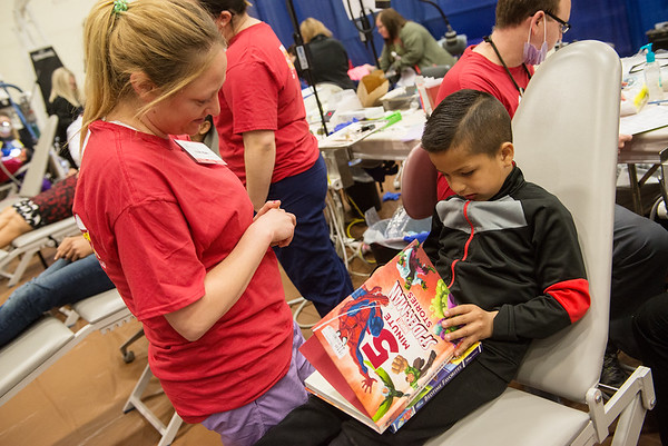 Jerson Morales, 7, Frontenac, looks at a storybook with Amanda Lillis, Blue Springs, on Friday during the Kansas Mission of Mercy free dental clinic at Pittsburg State University.<br /> Globe | Roger Nomer