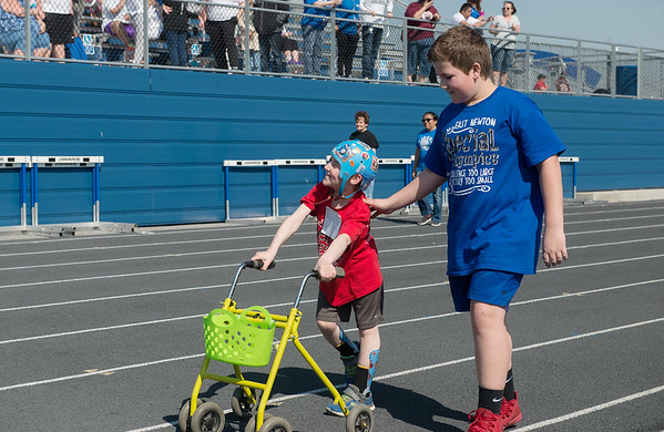 Thomas Perkins, 9, East Newton, acknowledges cheers from the crowd as he races with his buddy Jackson Cook, 14, East Newton during Tuesday's regional Special Olympics track meet at Carthage High School.<br /> Globe | Roger Nomer