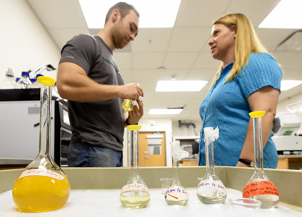 From the left: Missouri Southern student Cameron Priester and MSSU chemistry instructor Lynell Gilbert-Saunders stand near flasks containing liquified snail shells and elements found in mined areas on Wednesday afternoon. Snails are used as tests for soil and water quality in mined areas.<br /> Globe | Laurie SIsk