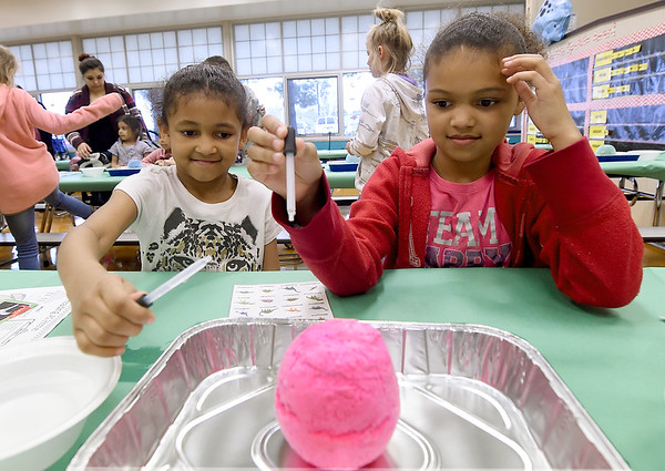 """From the left: Sisters Mesiyah Davis, 7 and Seriah Davis, 9, try to """"hatch"""" a baking soda dinosaur egg with diluted vinegar during a dinosaur themed family reading night on Thursday at McKinley School. The event featured a book fair, food, reading and more.<br /> Globe 