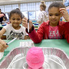 "From the left: Sisters Mesiyah Davis, 7 and Seriah Davis, 9, try to ""hatch"" a baking soda dinosaur egg with diluted vinegar during a dinosaur themed family reading night on Thursday at McKinley School. The event featured a book fair, food, reading and more.<br /> Globe 
