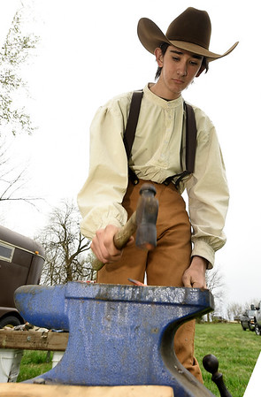 Elijah Balch, 16, of Newtonia, fashions a piece of hot metal into a hook during a blacksmithing demonstration on Saturday during the Fourth Annual Hammer In event on Saturday in Newtonia. The event featured Civil War reeanactors, blacksmiths, tours and more during the day long event.<br /> Globe | Laurie Sisk