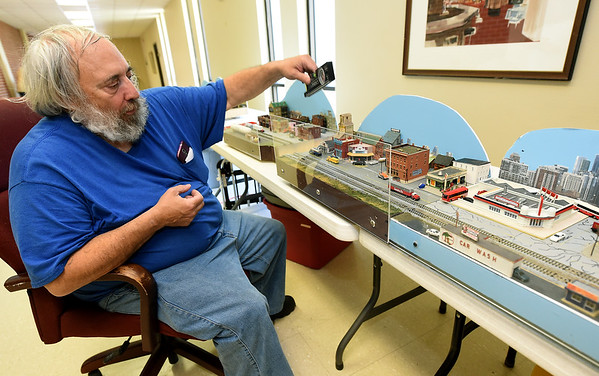 Model builder Fred Miller, of Reeds, pieces together a 20-foot cityscape display on Friday in preparation for the Joplin Museum Complex Model Railroad Show and Swap Meet. The show runs today from 9 a.m. to 3 p.m. at the museum. Proceeds from the event will benefit the museum.<br /> Globe | Laurie Sisk
