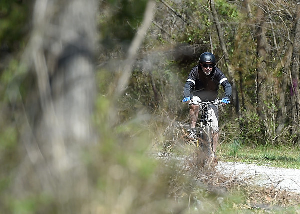 An unidentified cyclist makes his way along the Frisco-Greenway Trail near Division street on Wednesday. <br /> Globe | Laurie SIsk