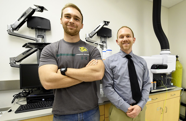 Missouri Southern student Cameron Priester and MSSU biology and environmental health instructor Kyle Gustafson stand beside an atomic emissions spectrometer on Wednesday afternoon in the MSSU biology department. The duo are analyzing liquified snails as tests for soil and water quality in mined areas.<br /> Globe | Laurie SIsk