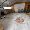 Aaron Dyer stands inside a gravel floor garage at his mother's rental property at 113 South Jackson on Tuesday. Dyer contends that while under management by Keller Williams Property Management's Steve Jones, homeless camps were set up inside out buildings and on the grounds of Kitty Dyer's property causing damage to the house and the grounds.<br /> Globe | Laurie Sisk
