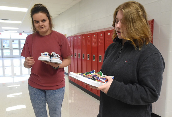 Carl Junction High School freshman Rachel Jones, right, talks about how her love of music influenced the design of her shoes as senior Theresa Rodriguez looks on Wednesday at CJHS. The duo are among 50 finalists nationwide in a contest that would benefit their art department with  $75,000 grand prize.<br /> Globe | Laurie Sisk
