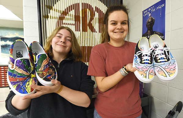 From the left: Carl Junction High School freshman Rachel Jones and senior Theresa Rodriguez on Wednesday hold prototypes of the Vans shoes they designed for a contest sponsored by the popular shoe company. At stake is a grand prize of $75,000 to the school's art department. Second place will be awarded $10,000.<br /> Globe | Laurie Sisk