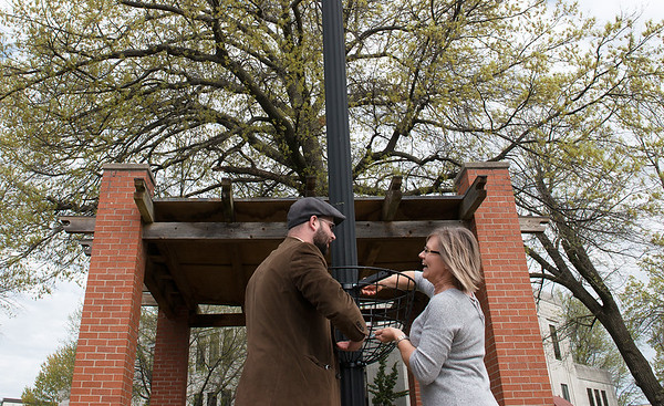 Justin Carnahan, vice president of the Neosho Chamber of Commerce, and Michele Buhr install at flower basket at the Newton County Courthouse on Friday.<br /> Globe | Roger Nomer