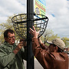 Rain Miljan, left, and Mike Chesnut install a flower basket on the square in Neosho on Friday.<br /> Globe | Roger Nomer