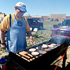 Stuart Payne, of the Carl Junction Lions Club, mans the grill as he prepares to feed about 35 volunteers from the Lions Club and LEO on Saturday at Irving Elementary.<br /> Globe | Laurie Sisk