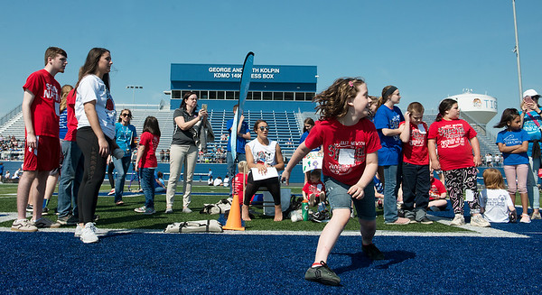 Paiton Deckard, 9, East Newton competes in the softball throw during Tuesday's regional Special Olympics track meet at Carthage High School.<br /> Globe | Roger Nomer