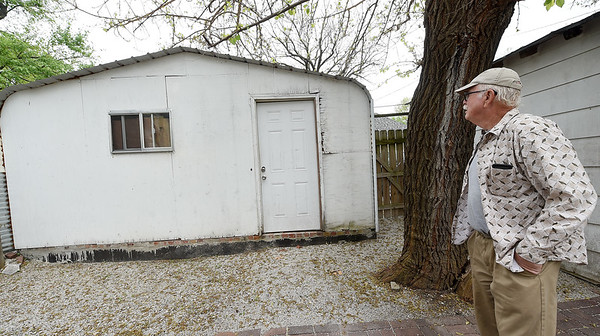 Dennis Burghart stands near a gravel floor garage at his wife's rental property at 113 South Jackson on Tuesday. Burghart contends that while under management by Keller Williams Property Management's Steve Jones, homeless camps were set up inside out buildings and on the grounds of Kitty Dyer's property causing damage to the house and the grounds.<br /> Globe   Laurie Sisk