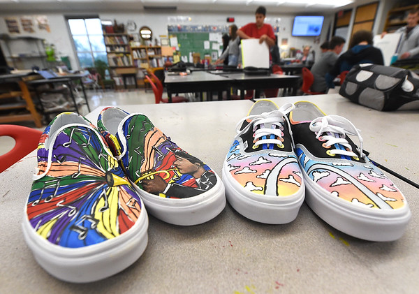From the left: Prototypes of the Vans shoes created by Carl Junction High School freshman Rachel Jones and senior Theresa Rodriguez sit in an art department classroom on Wednesday at Carl Junction High School.  The shoes are entered in a Vans' contest for a grand prize of $75,000 to the school's art department. Second place will be awarded $10,000. <br /> Globe | Laurie Sisk