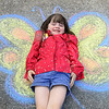 Alice Fletcher-Fierro, transforms from a five-year-old girl to a colorful butterfly, courtesy of some sidewalk chalk art at the May the Forest Be with You event on Saturday at Landreth Park. The event beagan with a 5K run, followed by luve entertainment, a native tree and plant sale, hikes, demonstrations, a clean up of Joplin Creek and more.<br /> Globe | Laurie Sisk