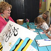 Clockwise, fom the left: Ann Leach visits with Cassie Estes, Adrianna Estes, 8 and Cadence Wumsett, 2, as they make birthday cards during the first anniversary of the Empire Market on Saturday at the market. The self-colored cards made by each child will arrive in their own mail on the ocassion of their birthdays this year. The event featured live music, prize drawings, food and more.<br /> Globe | Laurie Sisk