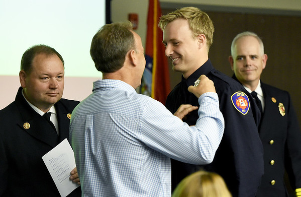 Retired Joplin Fire Department Captain Kevin Theilen, center left, pins a badge on his son, Koltyn Theilen during a JFD Recruit Graduation and Promotion Ceremony on Thursday at the Joplin Public Safety Training Center. Theilen was one of seven new additions to the department. Also pictured JFD Fire Chief James Fergurson, left, and JFD Fire Training Chief Mark Cannon, right. The other new firfighters are Justin Sellers, Spencer Dobbs, Jason Williams, Kevin Miller, Jacob Guernsey and Jeff Gallant.<br /> Globe | Laurie Sisk<br /> Globe | Laurie Sisk
