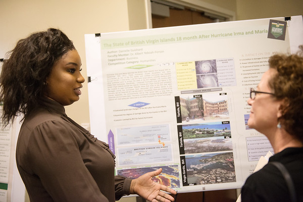 Danielle Guishard, a Missouri Southern senior from the British Virgin Islands, talks about her research with Ree Wells-Lewis, a sociology professor at MSSU, during Wednesday's Student Research Symposium at MSSU.<br /> Globe | Roger Nomer