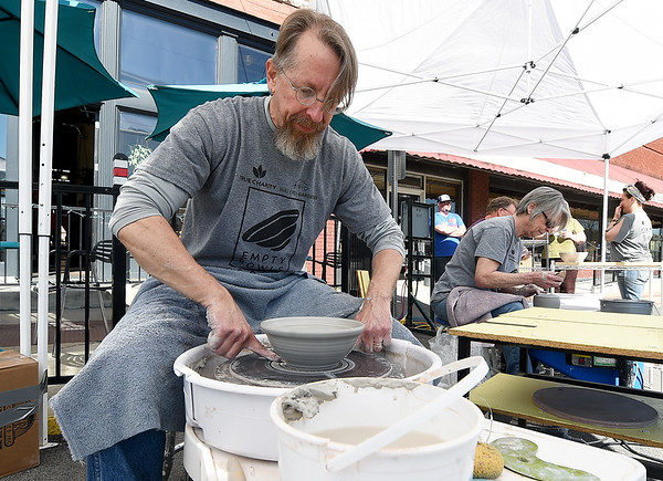Jeffrey Jones, owner of Clay Cup pottery and coffee shop in Neosho fashions a bowl for the Empty Bowls project on Saturday outside his business near the square during the Empty Bowl-A-Thon. Volunteers hope to have 1,000 bowls ready for the November event and on Saturday, artists enjoyed the cameraderie of pottery, live music, food trucks and more. Proceeds from the November event will benefit Watered Gardens, Mission Joplin and We Care of the Four States.<br /> Globe | Laurie Sisk
