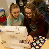 Gracie Edwards, Joplin High sophomore, left, and Hannah Hilsabeck, junior, work with a sewing machine on Wednesday at Joplin High.<br /> Globe | Roger Nomer