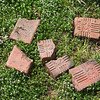 Bricks formerly used for a sidewalk on Joplin Street are discarded in a yard on Tuesday.<br /> Globe | Roger Nomer