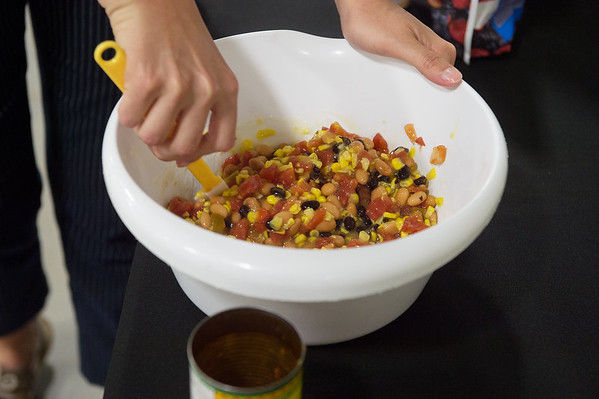 Lindsey Stevenson, with the University of Missouri Extension, mixes a canned bean salad on Monday at the Lion Co-op at Missouri Southern.<br /> Globe | Roger Nomer