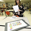 Carl Junction art teacher Nellie Mitchell stands near mock ups for Vans shoes created by freshman Rachel Jones and senior Theresa Rodriguez on Wednesday at CJHS. Jones and Rodriguez designed shoes for a contest sponsored by the popular shoe company. At stake is a grand prize of $75,000 to the school's art department. Second place will be awarded $10,000.<br /> Globe | Laurie Sisk