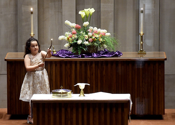 Seven-year-old Jessica Trimble serves as acolyte during Maunday Thursday Service on Thursday night at First Community Church. The service is one of many planned services in local houses of worship throughout the area this weekend.  <br /> Globe | Laurie Sisk