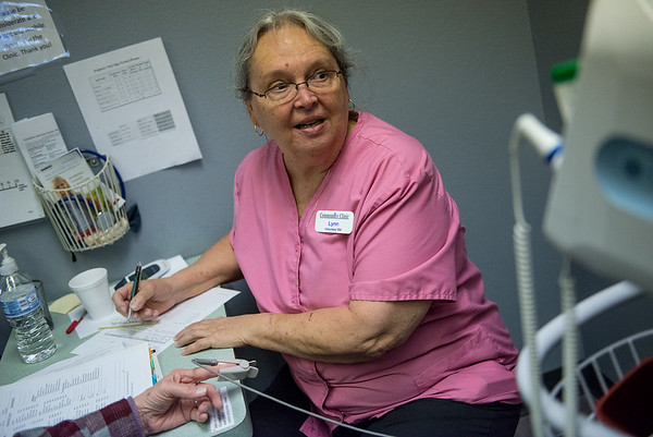 Lynn Fields, volunteer at the Joplin Community Clinic, checks in a patient on Monday at the clinic.<br /> Globe | Roger Nomer