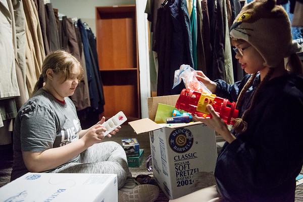 Rebecca Guerr, left, and Catie Tyurikov, seventh graders at Martin Luther School, help sort toys at Souls Harbor on Thursday. Students from the school brought Easter baskets of hygiene products and towels, and then spent the morning helping at Souls Harbor's store.<br /> Globe | Roger Nomer
