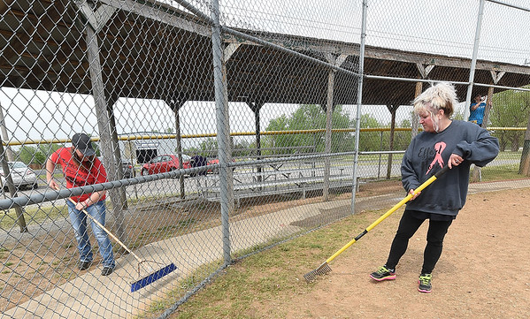 From the left: AT&T employees Cynthia Williams and Roxanne Isley clean the grounds on Tuesday afternoon at the old Redden Field. The field is the last free-use ball field in Joplin and AT&T employees welcome members of the community to help restore the field on Saturday.<br /> Globe | Laurie Sisk