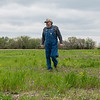 Darvin Bentlage walks through his property that borders a corporate hog farm near Golden City on Thursday.<br /> Globe | Roger Nomer