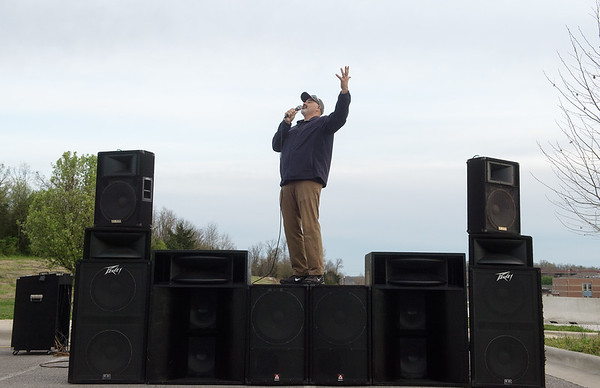 Frank Vazquez welcomes people to a music worship event in Mercy Park on Wednesday evening. Vazquez is a local DJ who helped organize the outdoor event and brought his music equipment for the worship songs.<br /> Globe | Roger Nomer