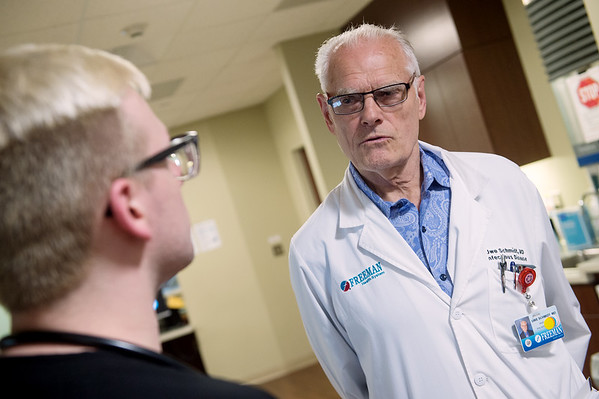 Uwe Schmidt (right), infectious disease specialist, talks with Tony Milano, registered nurse in transitional care, about a patient on Thursday at Freeman Hospital.<br /> Globe | Roger Nomer