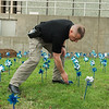 David McGough, Joplin police detective, arranges pinwheels in a display about child abuse awareness at the Joplin Police Department on Thursday.<br /> Globe | Roger Nomer