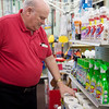 Harold Berger, owner of Pearl Bros. True Value Hardware, arranges cleaning supplies at the store on Monday in Joplin.<br /> Globe | Roger Nomer