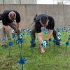 David McGough (left) and Dustin Moyer, Joplin police detectives, arrange pinwheels in a display about child abuse awareness at the Joplin Police Department on Thursday.<br /> Globe | Roger Nomer