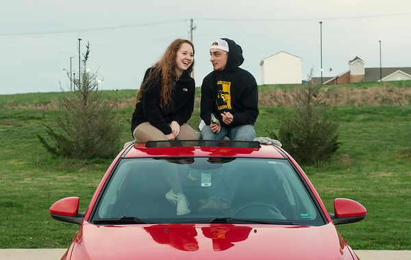 Asia Huffman and Austin Hendrix listen to worship music from their car during an outdoor event at Mercy Park on Wednesday.<br /> Globe | Roger Nomer