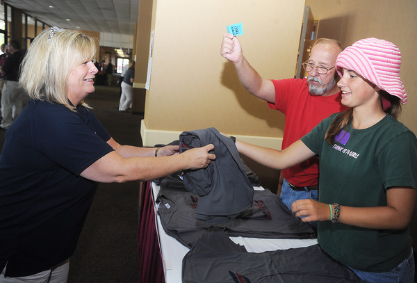 Globe/Roger Nomer<br /> Traci House, technology director at the administration building, gets a t-shirt from David Bjorkman and Ali Griffin, 15, volunteers from Lynnfield, Mass., following Monday's rally at the Holiday Inn Convention Center.