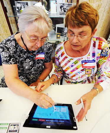 Globe/T. Rob Brown<br /> Supervisory election judge Mary Holland, left, and election judge Courtney Dermott sign off on the Jasper County Voter Confirmation system via an iPad Tuesday afternoon, Aug. 7, 2012, at the Donald Clark building polling location in Joplin.