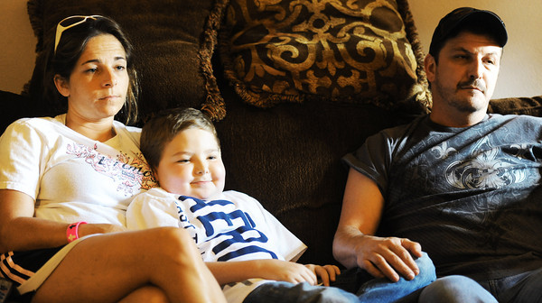 Globe/T. Rob Brown<br /> Ten-year-old Dylan Waggoner, of Webb City, sits with his parents, Heather Collins and Ronnie Waggoner, both of Webb City, Tuesday afternoon, Aug. 21, 2012, in his Webb City home. Young Waggoner is in need of a heart transplant.