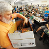Globe/T. Rob Brown<br /> Standing atop a chair, John Davidson, of Joplin, owner of Changing Hands Book Shoppe, auctions off a box of collectible card games Saturday afternoon, Aug. 4, 2012, during the downtown Joplin store's quarterly Game-A-Thon. The store holds an all-day game event and auction the first Saturday of February, May, August and November.