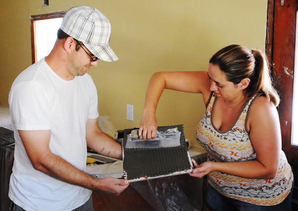 Globe/T. Rob Brown<br /> Nathan and Kelly Johnston, of Pittsburgh, Pa., help install ceramic tiles Friday morning, Aug. 10, 2012, at a tornado-damaged home in the 1200 block of Katherine in Duquesne. The newlyweds decided to spend their honeymoon working to help rebuild Joplin. They said they had been to Joplin last year while they were engaged to help with the rebuilding effort as well.