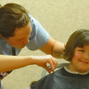 Globe/Roger Nomer<br /> Madison Hemby, 7, gets a hair cut from Savannah Hedge at the South YMCA on Saturday afternoon.  Stylists from New Dimensions were on hand to give free hair cuts for the upcoming school year.
