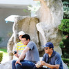 Globe/T. Rob Brown<br /> Giao Nguyen, right, takes a break from the heat by relaxing with a Vietnamese beverage in the shade of a stone garden with his sons Bao Nguyen, 12, left, and Jon Nguyen, all of Denver, Colo., during Marian Days Thursday morning, Aug. 2, 2012, in Carthage.