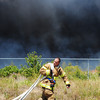 Globe/T. Rob Brown<br /> A Joplin firefighter moves his hoses to a new position to fight a portion of a controlled burn that moved into a grassy field just south of the old Route 66 Speedway Thursday afternoon, Aug. 30, 2012.