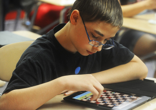 Globe/Roger Nomer<br /> Seventh grader Matthew McCauley plays a game of checkers on his new iPad at Baxter Springs Middle School.